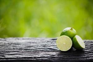 Green lemon sliced on wood photo