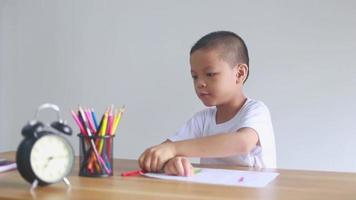 boy sitting and doing homework, drawing, coloring video