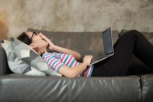 con sueño trabajando en casa, acostado y bostezando en el sofá de la sala. foto