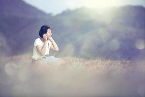 Young asian girl listening music by headphone in garden. photo