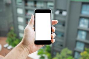 imagen de maqueta de la mano del hombre que sostiene el teléfono inteligente con pantalla en blanco. foto