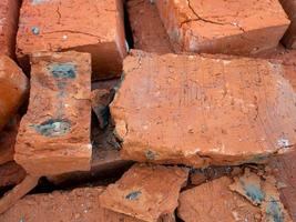 Red cracked brick of poor quality with black spots photo