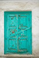 Persianas de madera vieja, pintura agrietada, cerrada con una viga transversal de hierro foto