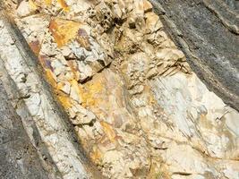 Mountain rock of gray, white, brown color stones in layer diagonally photo