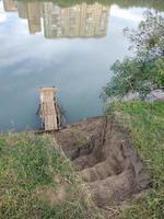 Pasos hacia el puente de pino sobre el río y el reflejo de las casas. foto