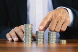 Businessman touch on coins stack on wooden table photo