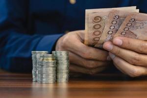 Centrarse en la pila de monedas sujetar la mano de billetes de baht tailandés antecedentes foto