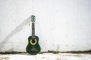 A small ukulele leans against a white wall photo