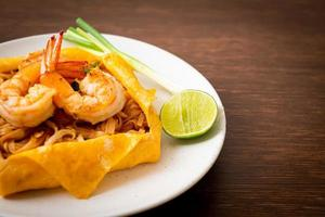 Thai stir fried noodles with shrimps and egg wrap photo