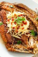 Fried Sea Bass Fish with Fish Sauce and Spicy Salad photo
