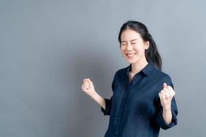 Asian woman rejoicing her success and victory clenching with joy photo