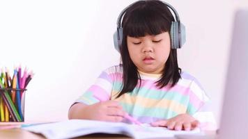 Asian female student wearing headphones studying online from home video