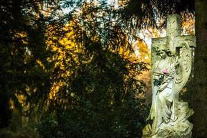 símbolo del cristianismo madre maría escultura en el cementerio foto