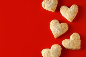Galletas de azúcar en forma de corazón sobre fondo rojo. foto