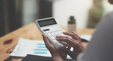 Close up Businesswoman using calculator and laptop photo