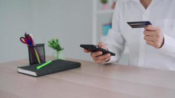 les hommes détiennent des cartes de crédit et utilisent leurs smartphones pour faire leurs achats en ligne. video