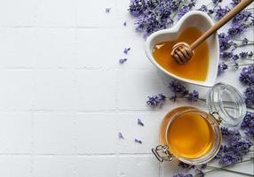Tarro y cuenco con miel y flores frescas de lavanda. foto