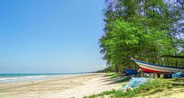 A fishing boat under some trees near beach photo