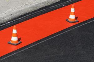 Pilones rojos y blancos en una pista para bicicletas recién marcada en rojo foto