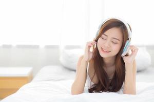 Joven mujer asiática disfruta de escuchar música con auriculares foto