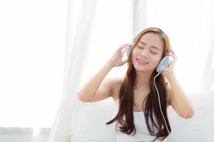 Joven mujer asiática disfruta de escuchar música con auriculares en el dormitorio foto