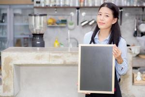mujer asiática es un empleado de pie sosteniendo la pizarra foto