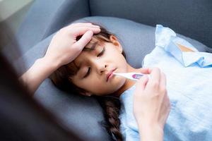 La mano de la madre tomando la temperatura con la niña es una enferma tendida en el sofá foto