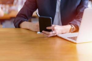 Young woman using smart phone on her desk photo
