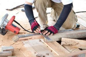 Carpenter man measuring plank wood photo