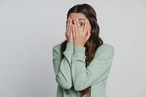 Beautiful girl closes her eyes with her hands photo