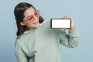 Pretty teenage girl holding a smartphone in her hands photo
