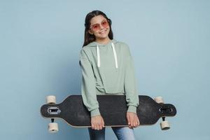 Beautiful, positive girl in sunglasses holding a skate in her hands photo