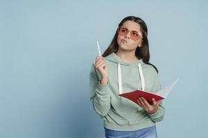 Cute teenage girl in sunglasses holding a notebook photo