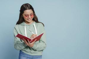 Smiling, cute teenage girl in sunglasses holding a notebook photo