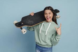 Positive, naughty girl holding a skate on her shoulder photo