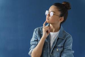 Dreamy, cute teenage girl with glasses touches her chin, looks away photo