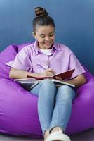 Attractive, positive teenage girl sitting in a comfortable pouf photo