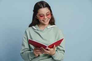 Positive, smiling girl writes something in a notebook photo