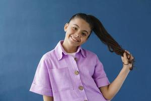 Smiling, positive teenage girl playing with her hair photo
