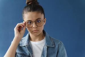 Serious teenage girl adjusts glasses looking at camera photo