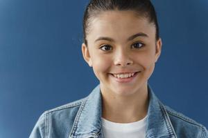 Positive teenage girl smiling beautifully, looking at camera photo