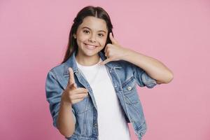 Teen girl shows a gesture to call back, points a finger photo
