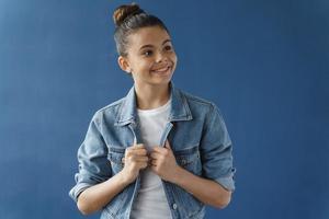 Positive teenage girl with glasses looks away photo