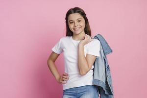 Attractive teenage girl holding jeans jacket on her shoulders photo