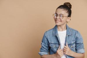 Teenage girl in glasses posing on a brown background photo