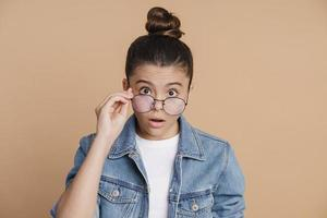 Shocked girl looks through glasses in surprise photo