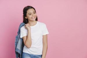 Beautiful teenage girl holding a denim jacket on her shoulders photo