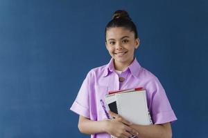 Smiling teenage girl posing with workbooks on blue background photo
