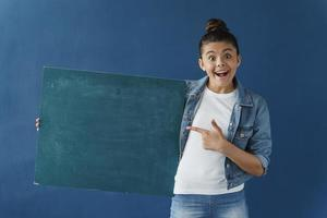 Attractive teenage girl holding a blank blue paper, copy space photo