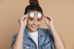 Cute, attractive teenage girl adjusts glasses photo